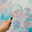 Hand holding Magnifying glass with map background — Stock Photo #33168359