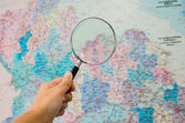Hand holding Magnifying glass with map background — Stock Photo