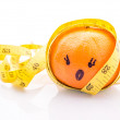 Funny face Orange with yellow measuring tape wrapped around it. — Stock Photo #33178885