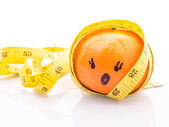 Funny face Orange with yellow measuring tape wrapped around it. — Stock Photo