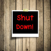 Text shut down on the black photo with wooden background — Stock Photo