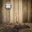 Old clock on grungy wooden wall and brick floor — Stock Photo
