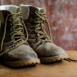 A pair of dirty boot on wooden background — Stock Photo