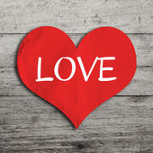 Love word on red heart shape with wooden wall — Stock Photo