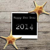 Happy New Year 2014 on Star fish and card on a wooden boards. — Stock Photo