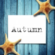 Note paper and autumn message,Star fish on wooden boards — Stock Photo