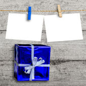Blue gift box on wooden wall with a blank paper hanged — Stock Photo