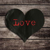Love word on black heart shape with wooden wall,broken heart con — Stock Photo