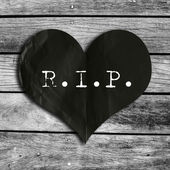 R.I.P. word on black heart shape with wooden wall,broken heart c — Stock Photo