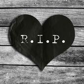 R.I.P. word on black heart shape with wooden wall,broken heart c — Fotografia Stock