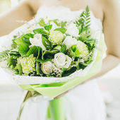 Bride is holing wedding flowers. Focus on flowers. — Stock Photo