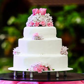 White four tiered wedding cake on table — Zdjęcie stockowe