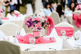 Wedding flowers - tables set for fine dining — Stock Photo