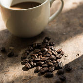 Cup of coffee and coffee bean on wooden background with nature l — Stok fotoğraf