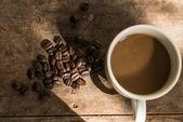 Tasse kaffee und kaffeebohnen auf hölzernen hintergrund mit natur l — Stockfoto