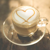 Heart shape on creamy coffee with natural light. — Photo