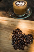 Heart shape of coffee beans and a cup of coffee on wooden backgr — Foto Stock
