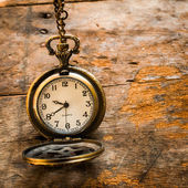 Vintage pocket watch on chain on wooden background with still li — 图库照片