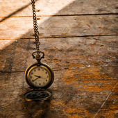 Vintage pocket watch on chain on wooden background with still li — ストック写真