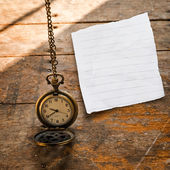 Vintage pocket watch on chain and torn paper on wooden backgroun — Stock Photo