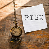 Risk message on Vintage pocket watch on chain and torn paper on — Stock Photo