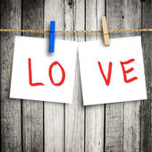Love on note paper attach to rope with clothes pins on wooden ba — Stock Photo