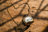 Heart pocket watch on a wood background with natural light. — Stock Photo