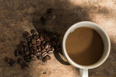 Cup of coffee and coffee bean on wooden background with nature l — Stock Photo