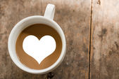 Cup of love coffee on wooden background with nature light. — Stock Photo