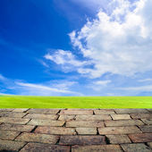 Concrete pacement with grass field on blue sky background — Stock Photo