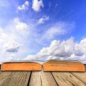 Otevřít knihu na dřevěné podlaze s modrou oblohou — Stock fotografie