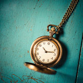 Old style pocket watch on blue wooden background — Stock Photo
