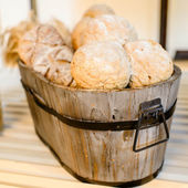Variety of bread in basket on wooden shelf. — Stock Photo