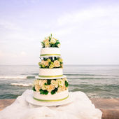 White and roses wedding cake by the beach — Zdjęcie stockowe