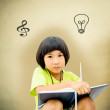 Cute little girl writing her homework on brown background — Stock Photo #42701763