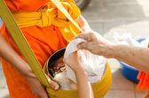 Setzen sie lebensmittel-angebote in ein buddhistischer mönch almosen schüssel — Stockfoto