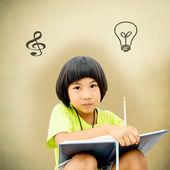 Cute little girl writing her homework on brown background — Stockfoto