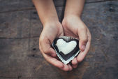 Love note on black and white chocolate in kid's hand — Stock Photo