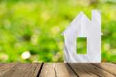 White paper house and spring green grass with green bokeh and su — Stock Photo