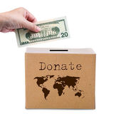 Human hand putting money in brown donate box with world map eart — Stock Photo