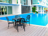 Black table and chairs near a cool pool — Stock Photo