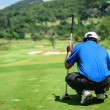 Golf player with putter squatting to analyze the green at golf course — Stok fotoğraf