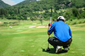 Golf player with putter squatting to analyze the green at golf course — Stock Photo