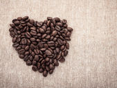 Coffee Beans with heart shape on brown fabric — Stock Photo