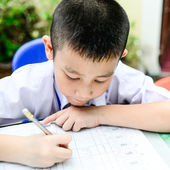 Asian kid do home work in classroom — Photo