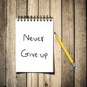 Never give up message on Notebook with pencil on wooden backgrou — Stock Photo