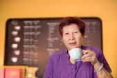Asian senior woman enjoying cup of tea in coffee shop. — Стоковое фото
