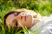 Red-haired woman lying on the  grass at sunny day — Foto Stock