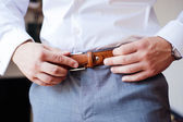 Groom preparing for the wedding ceremony dress belts — Stock Photo