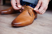 Groom preparing for the wedding ceremony tying shoelaces — Stock Photo